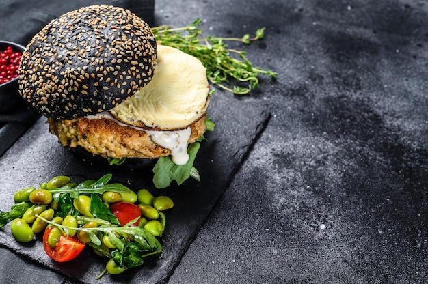 Домашний бургер с черной булочкой, яичницей и рукколой. blackburger. вид сверху. копировать пространство
