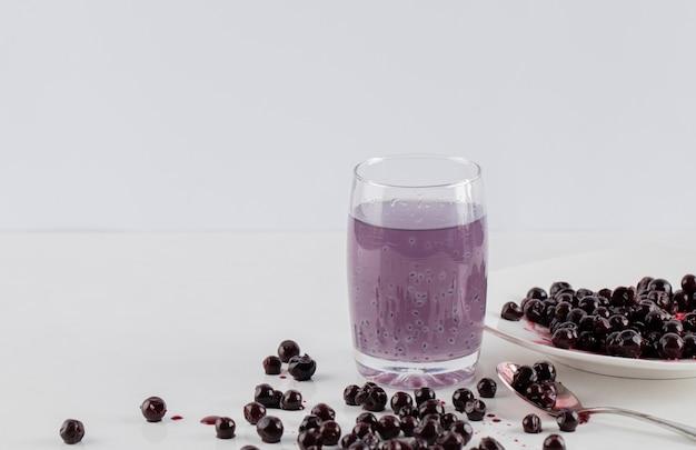 Confettura di ribes nero in un piattino bianco con un bicchiere di succo intorno.