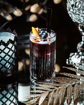 Blackcurrant juice in a glass with a straw