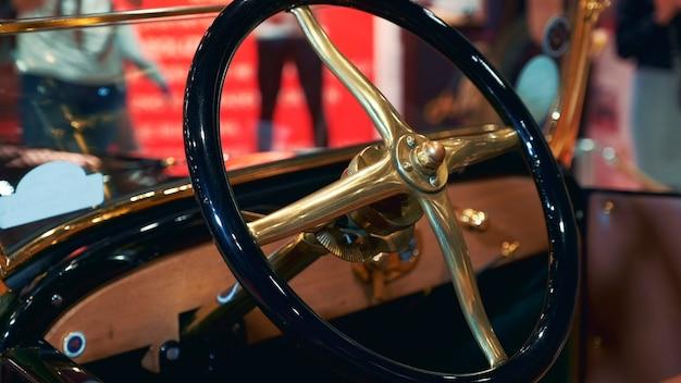 レトロな車のクローズアップビューのブラックゴールデンステアリングホイール
