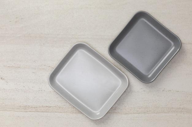 白い石blackground、伝統的な手作りの台所用品の概念の平面図に空の空セラミック正方形プレートのグループ