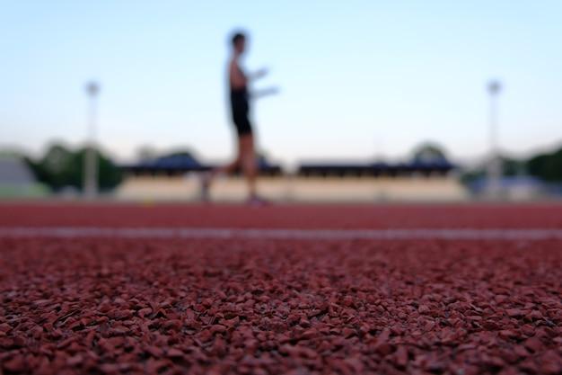 ランニングとジョギングのための赤い床の競技場の人々はblackgroundをぼやけました。