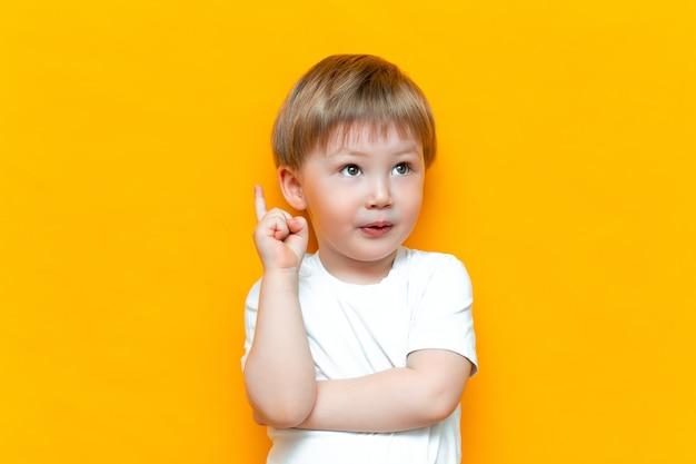 Портрет милого красивого белокурого мальчика с пальцем указал вверх. у маленького ребенка есть идея. малыш, изолированные на желтом blackground. успех, блестящая идея, креативные идеи