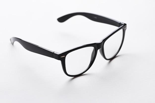 白い背景の上の黒い縁のメガネ