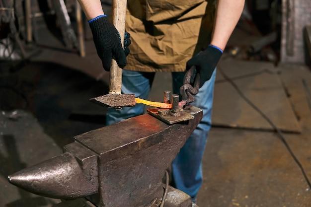 Кузнец выковывает подкову на наковальне с помощью гнутой вилки, крупный план
