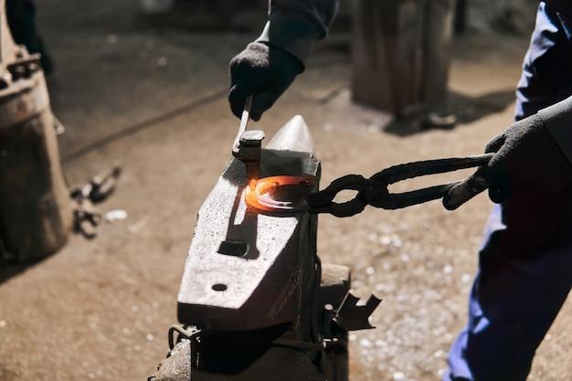 鍛冶屋は鍛造ノミでアンビルに馬蹄形を鍛造、クローズアップ