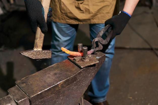 Кузнец выковывает подкову на наковальне с помощью выносливого инструмента, крупный план