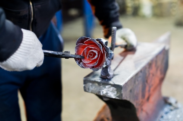 Blacksmith forges steel rose on the anvil