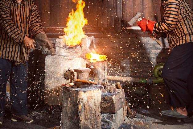 Blacksmith forging the molten metal with a hammer to make keris