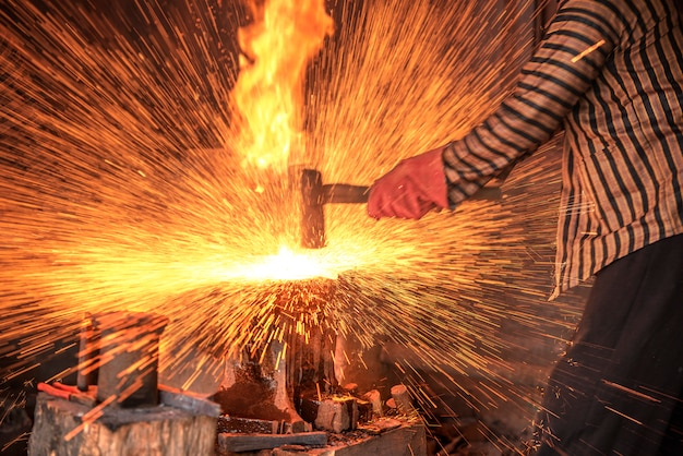 Blacksmith forging the molten metal with a hammer to make keris