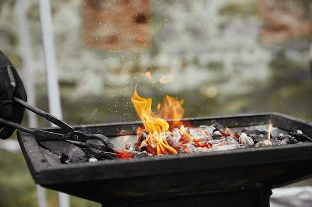 Fabbro riscaldamento pezzo di metallo nel carbone ardente