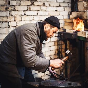 鍛冶屋は、アンビルに溶銑を芸術的に鍛造します。