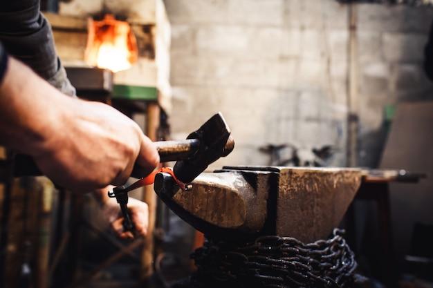 Кузнец выполняет художественную ковку горячего металла на наковальне.