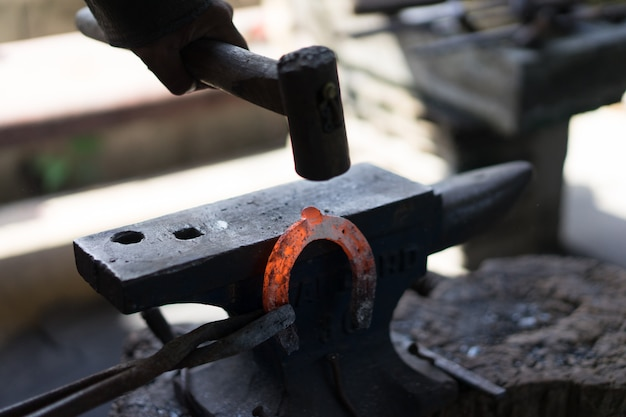 A blacksmith makes a horseshoe with a hot iron.