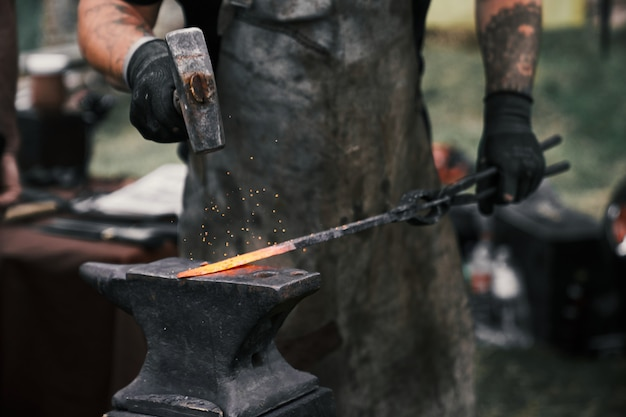 Blacksmith manually forging molten metal on anvil