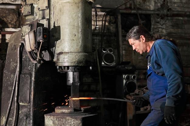 Кузнец обрабатывает горячую заготовку механическим молотком в мастерской.