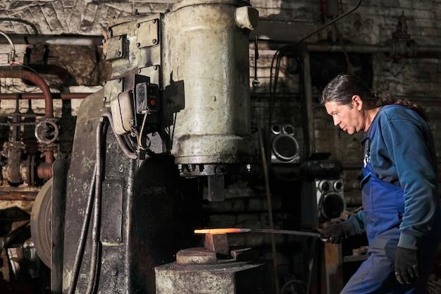 Кузнец обрабатывает горячую заготовку пневмомолотом в мастерской.