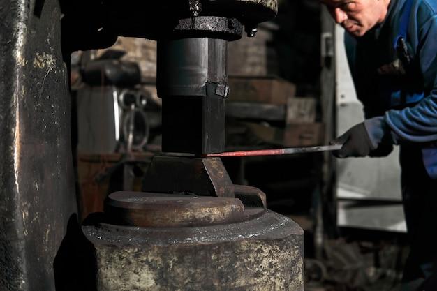 Кузнец обрабатывает горячую деталь силовым молотком в мастерской.