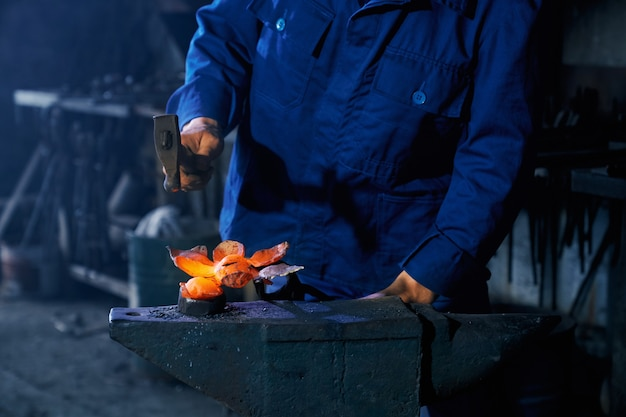 溶湯を鍛造するために重いハンマーを使用する鍛冶屋