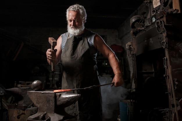 Кузнец с кисточкой обрабатывает расплавленный металл