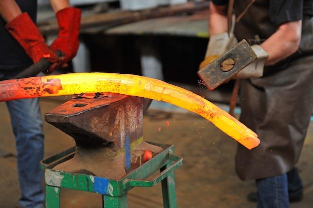 대장장이는 모루에서 용융 금속을 수동으로 단조합니다.
