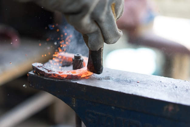 Blacksmiths working in the forge and making a horseshoe.
