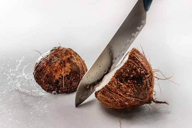 The blade of the knife cuts the coconut into two halves. visible splashes on a light background.