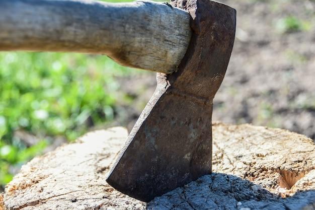 Лезвие топора торчит в деревянном пне, дровосек, вырубает деревья, страх, насилие, преступность, копирует пространство