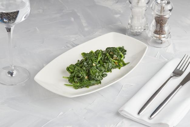 데친 시금치 잎 접시, 밝은 배경