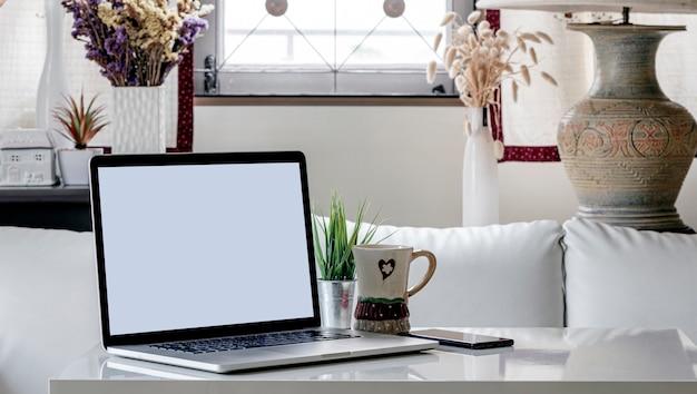 リビングルームの白い木製のテーブルにブランドの画面のノートパソコン。