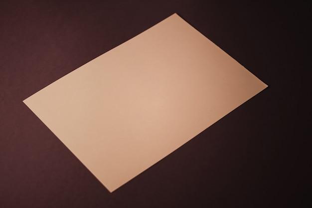 オフィスステーショナリーフラットレイラグジュアリーブランディングフラットレイとブラとして暗い背景に紙のベージュを空白にします...