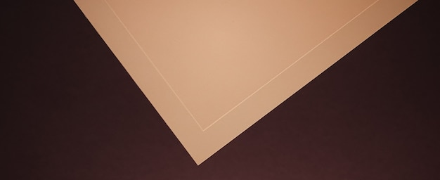 Пустая бумага бежевого цвета на темном фоне, как офисные канцелярские принадлежности, роскошный брендинг, плоская планировка и бюстгальтер ...