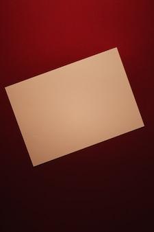 オフィスステーショナリーフラットレイラグジュアリーブランディングフラットレイと...として濃い赤の背景に紙ベージュを空白にします。