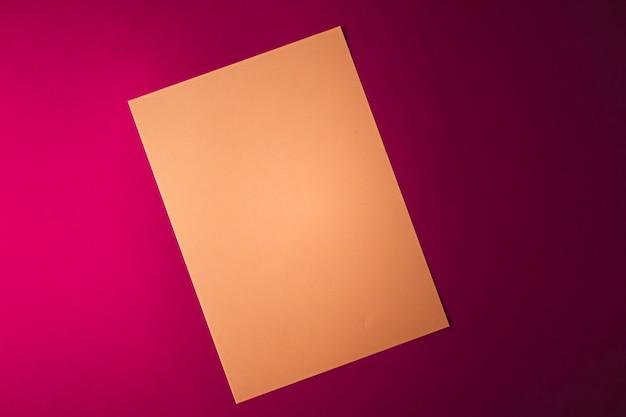 Пустая бумага коричневого цвета на розовом фоне в виде офисных канцелярских принадлежностей, роскошных брендов, плоской планировки и бюстгальтера ...