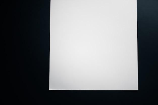 オフィスステーショナリーフラットレイラグジュアリーブランディングフラットレイとbr ...として黒の背景に白の紙を空白にします。