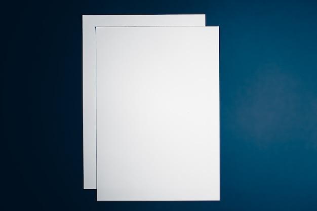 オフィスステーショナリーフラットレイラグジュアリーブランディングフラットレイとブラとして青い背景に白い紙を空白にします...