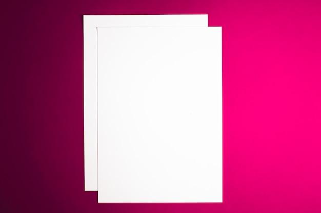 ピンクの背景に白い紙を空白にして、オフィスステーショナリーフラットレイラグジュアリーブランディングフラットレイとブラ...