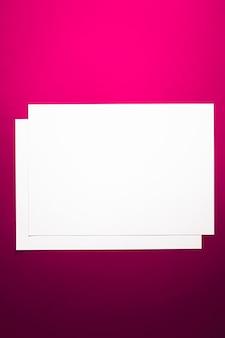 オフィスステーショナリーフラットレイラグジュアリーブランディングフラットレイとブラとしてピンクの背景に白の紙を空白にします...