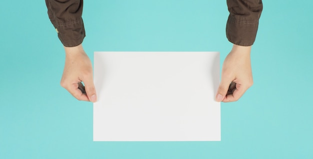 Пустая бумага a4. пустая белая доска в руке человека и носить темно-синюю рубашку на зеленой мятой или синем фоне тиффани.