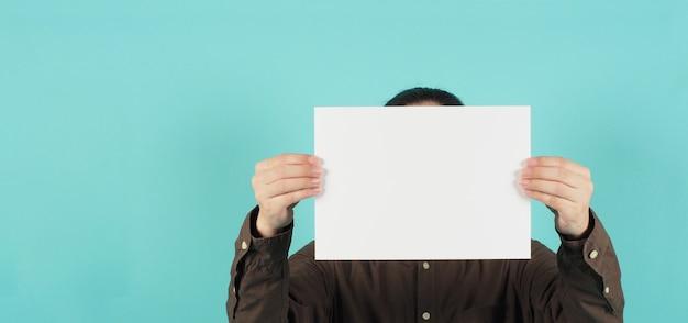 Пустая бумага формата а4. пустая белая доска в руке человека закрыла лицо и носит темно-синюю рубашку на зеленой мятой или синем фоне тиффани.