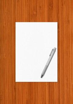 Чистый лист бумаги a4 и ручка на темном деревянном фоне