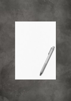Blank a4 paper sheet and pen mockup template isolated on dark concrete background