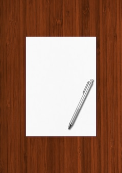 Blank a4 paper sheet and pen mockup template isolated on dark wooden background