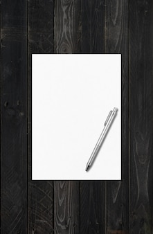 Blank a4 paper sheet and pen  template isolated on black wood background