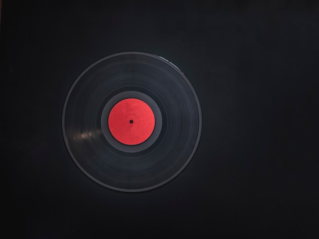 Blank abstract vinyl record without text on black dark surface with copy space