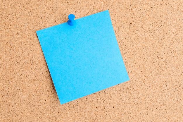 푸시 핀이있는 코르크 메시지 보드에 부착 된 빈 접착 메모
