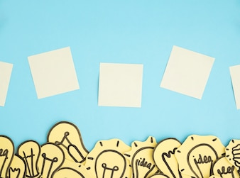Blank adhesive notes over the border of many light bulbs against blue background