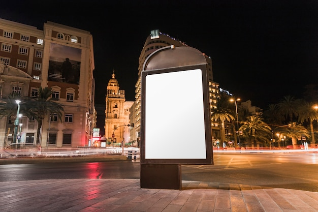 Blank advertisement billboard in front of building at night