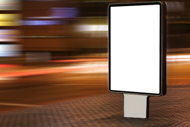Blank advertisement board on street at night