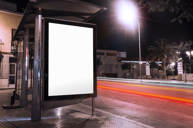 Blank advertisement at bus shelter with blurred traffic lights at night